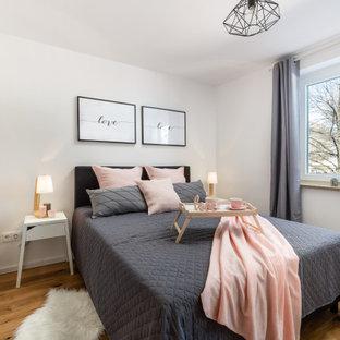 Mittelgroßes Skandinavisches Schlafzimmer mit weißer Wandfarbe, braunem Holzboden und braunem Boden in München