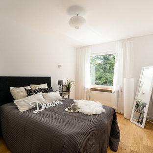 Mittelgroßes Klassisches Schlafzimmer mit weißer Wandfarbe, braunem Holzboden und braunem Boden in München