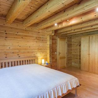 Diseño de dormitorio principal, rústico, grande, sin chimenea, con paredes marrones y suelo de madera clara