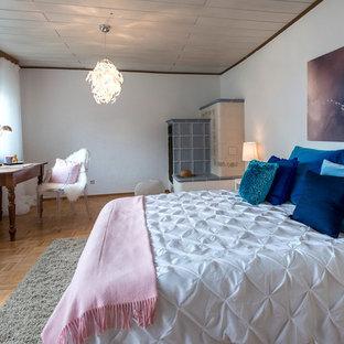 Foto de dormitorio principal, clásico renovado, grande, con paredes blancas, suelo de madera en tonos medios, suelo marrón, estufa de leña y marco de chimenea de baldosas y/o azulejos