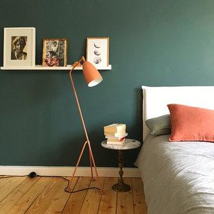 Modelo de dormitorio principal, escandinavo, de tamaño medio, sin chimenea, con paredes verdes, suelo de madera clara y suelo beige