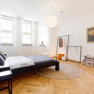Modernes Schlafzimmer mit weißer Wandfarbe, braunem Holzboden und braunem Boden in Essen