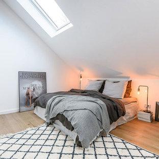 Kleines Nordisches Hauptschlafzimmer ohne Kamin mit weißer Wandfarbe, braunem Holzboden und braunem Boden in München