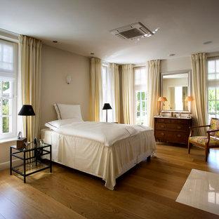 Modelo de dormitorio principal, exótico, grande, con paredes beige, suelo de madera en tonos medios, chimenea tradicional y marco de chimenea de piedra