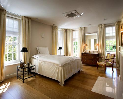 Großes Tropenstil Hauptschlafzimmer Mit Beiger Wandfarbe, Braunem  Holzboden, Kamin Und Kaminsims Aus Stein In