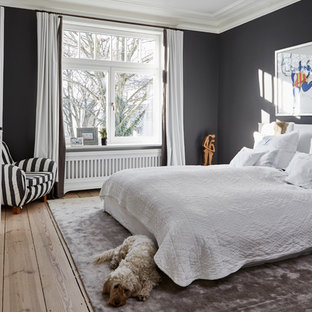 Modelo de dormitorio principal, contemporáneo, grande, con paredes negras, chimenea tradicional, marco de chimenea de madera, suelo marrón y suelo de madera en tonos medios