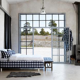 На фото: спальня среднего размера в стиле лофт с печью-буржуйкой, бетонным полом и серыми стенами с