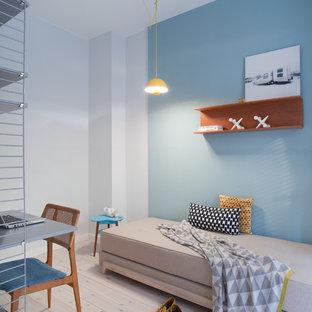 Imagen de habitación de invitados escandinava, pequeña, sin chimenea, con paredes azules y suelo de madera clara