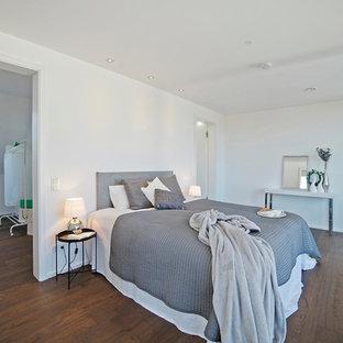 Mittelgroßes Modernes Hauptschlafzimmer ohne Kamin mit weißer Wandfarbe, braunem Holzboden und braunem Boden in München