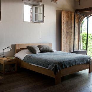 Imagen de dormitorio urbano, grande, con paredes blancas, suelo de madera oscura, chimenea tradicional y marco de chimenea de piedra