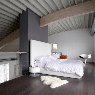Ejemplo de dormitorio tipo loft, industrial, extra grande, sin chimenea, con suelo de madera oscura, paredes blancas, marco de chimenea de yeso y suelo marrón