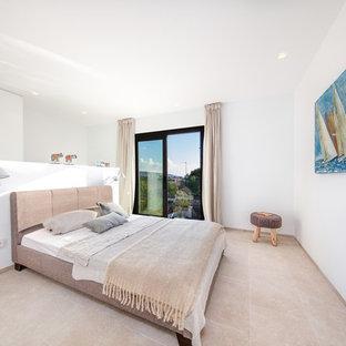 Ejemplo de habitación de invitados costera, grande, sin chimenea, con paredes blancas y suelo de mármol