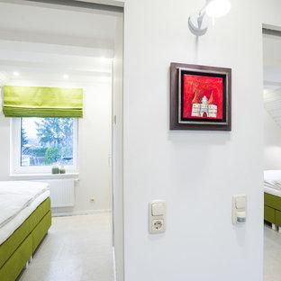 Immagine di una camera da letto design di medie dimensioni con pareti bianche, pavimento in sughero e pavimento bianco