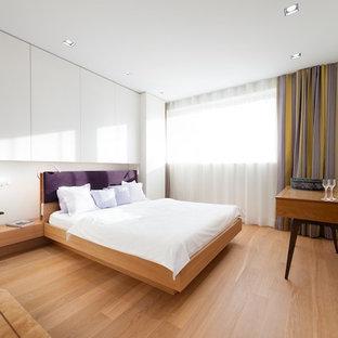 Immagine di una camera matrimoniale contemporanea di medie dimensioni con pareti bianche, pavimento in legno massello medio e nessun camino