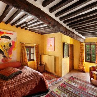 Diseño de dormitorio principal, mediterráneo, de tamaño medio, sin chimenea, con paredes amarillas y suelo de baldosas de terracota