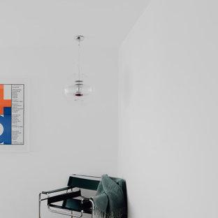 Modelo de dormitorio moderno, grande, con paredes blancas, suelo de madera oscura, estufa de leña, marco de chimenea de yeso y suelo marrón