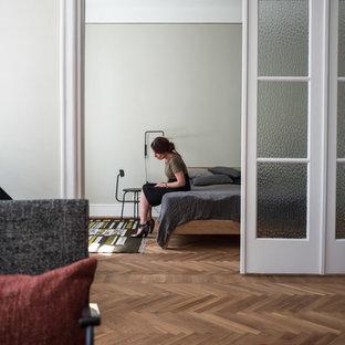 Modelo de dormitorio principal, escandinavo, de tamaño medio, con paredes verdes, suelo de madera clara, marco de chimenea de madera y suelo blanco