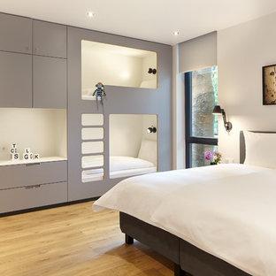 Mittelgroßes Modernes Gästezimmer ohne Kamin mit weißer Wandfarbe, hellem Holzboden und beigem Boden