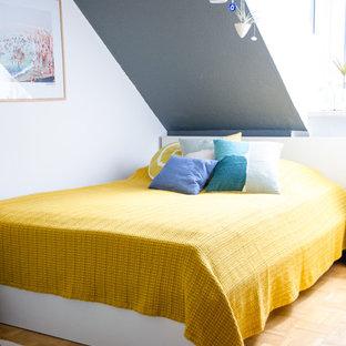Immagine di una camera degli ospiti moderna con parquet chiaro, pareti grigie e nessun camino