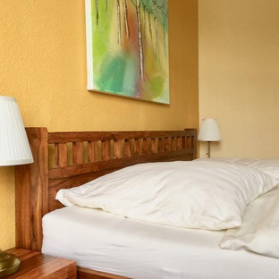 Imagen de dormitorio principal, tropical, pequeño, con paredes amarillas, suelo vinílico y suelo marrón