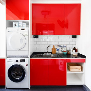 Design ideas for an eclectic utility room in Singapore with a submerged sink, flat-panel cabinets, red cabinets, white walls, a stacked washer and dryer, black floors and black worktops.