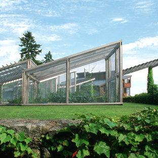 Foto på en funkis fristående garage och förråd, med växthus