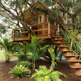 Foto på en stor tropisk fristående garage och förråd