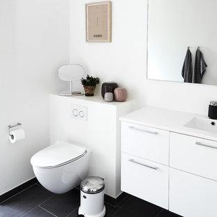 Свежая идея для дизайна: туалет среднего размера в скандинавском стиле с плоскими фасадами, белыми фасадами, инсталляцией, белыми стенами, полом из керамической плитки, монолитной раковиной, столешницей из ламината и серым полом - отличное фото интерьера
