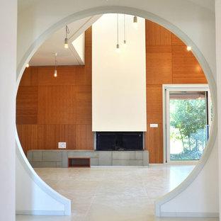 Imagen de salón abierto, minimalista, grande, con paredes marrones, chimenea lineal, marco de chimenea de yeso, suelo de cemento, televisor colgado en la pared y suelo blanco