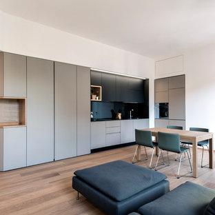 Ispirazione per un soggiorno design di medie dimensioni con parquet chiaro e pareti bianche