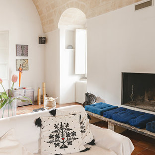 Example of a tuscan terra-cotta tile family room design in Other