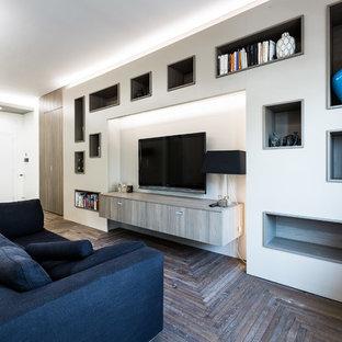 Modelo de sala de estar con biblioteca abierta, contemporánea, sin chimenea, con paredes blancas, suelo de madera oscura, televisor colgado en la pared y suelo azul