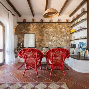 Réalisation d'une salle de séjour méditerranéenne avec un mur marron, un sol en carreau de terre cuite et un sol rouge.