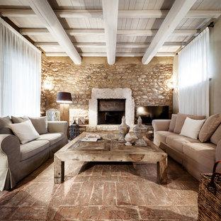 Immagine di un soggiorno country chiuso con pareti beige, camino classico, cornice del camino in pietra, TV autoportante e pavimento marrone