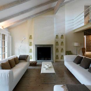 ミラノの大きい地中海スタイルのおしゃれなLDK (白い壁、淡色無垢フローリング、標準型暖炉、石材の暖炉まわり) の写真
