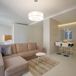 Imagen de sala de estar abierta, actual, con paredes blancas, suelo de cemento y suelo gris