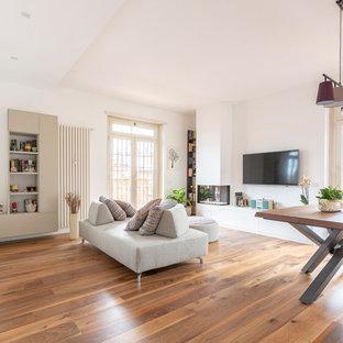 Foto di un grande soggiorno design aperto con pareti bianche, pavimento in legno massello medio, camino ad angolo, cornice del camino in metallo, TV a parete e pavimento marrone