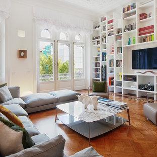 Modern inredning av ett separat vardagsrum, med ett bibliotek, vita väggar, mellanmörkt trägolv och en inbyggd mediavägg