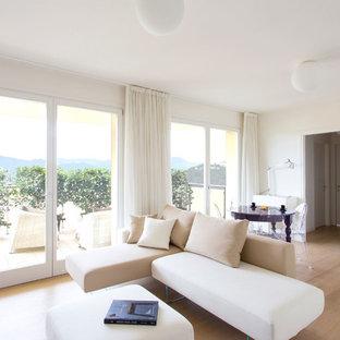 Esempio di un soggiorno minimal aperto con pareti bianche, parquet chiaro e pavimento beige
