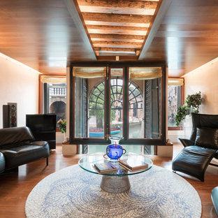 Immagine di un soggiorno design chiuso con pareti beige, pavimento in legno massello medio e pavimento marrone