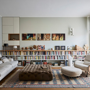 This is an example of a contemporary living room in Milan with multi-coloured walls, medium hardwood floors and brown floor.