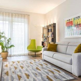 Immagine di un soggiorno design di medie dimensioni e chiuso con TV autoportante, nessun camino, pavimento marrone, pareti grigie e pavimento in legno massello medio