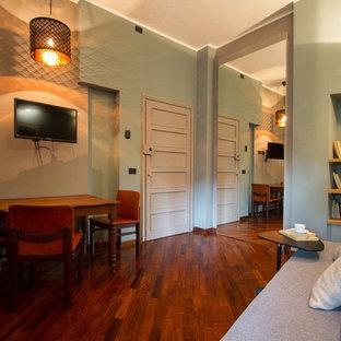 Ejemplo de sala de estar abierta, moderna, pequeña, con paredes multicolor, suelo de madera en tonos medios, televisor colgado en la pared y suelo marrón