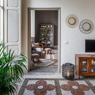 フィレンツェの中サイズのミッドセンチュリースタイルのおしゃれな独立型ファミリールーム (白い壁、大理石の床、据え置き型テレビ、マルチカラーの床) の写真