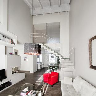 Idee per un soggiorno minimal di medie dimensioni e stile loft con pareti grigie, parquet scuro, camino bifacciale, cornice del camino in intonaco, TV autoportante e pavimento marrone