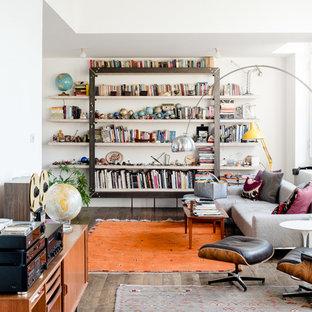 Imagen de sala de estar con biblioteca ecléctica, de tamaño medio, con paredes blancas, suelo marrón y suelo de madera oscura