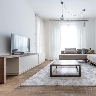 Immagine di un grande soggiorno minimalista con pareti bianche, pavimento in legno massello medio, TV autoportante e divano davanti alla finestra
