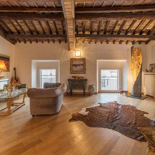 Immagine di un soggiorno mediterraneo con pareti beige, pavimento in legno massello medio, TV a parete e pavimento marrone