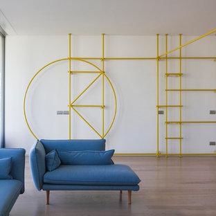 Ispirazione per un piccolo soggiorno industriale aperto con libreria, pareti bianche, pavimento in legno massello medio e pavimento marrone