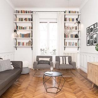 Réalisation d'un salon avec une bibliothèque ou un coin lecture nordique de taille moyenne avec un téléviseur fixé au mur, un mur blanc, un sol en bois brun et un sol marron.